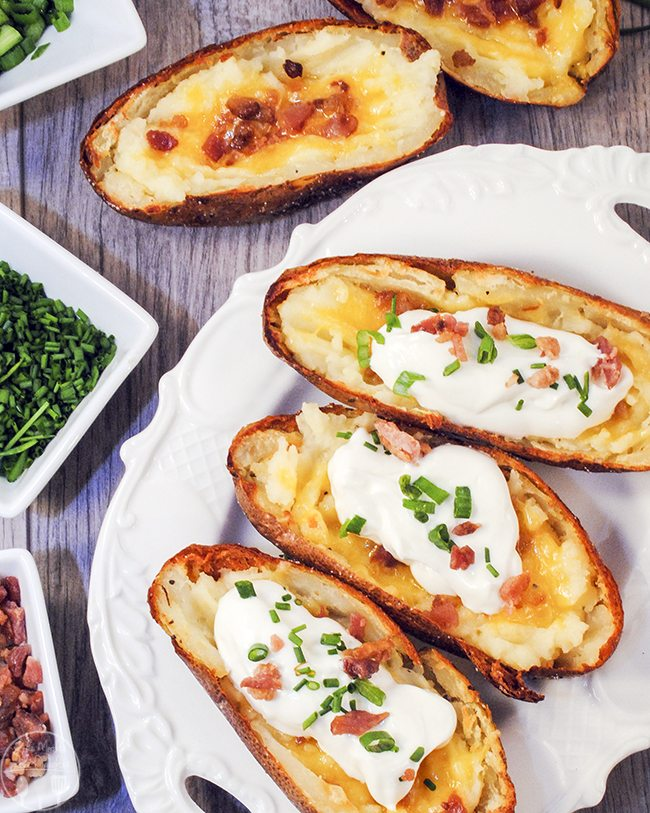Loaded Potato Skins - Roasted potato skins loaded with creamy mashed potatoes, sour cream, butter, cheese, topped with bacon bits, green onions, chives, and more cheese. A delicious side or appetizer.