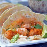 Shrimp taco with yogurt sauce, cilantro, and a side of lime