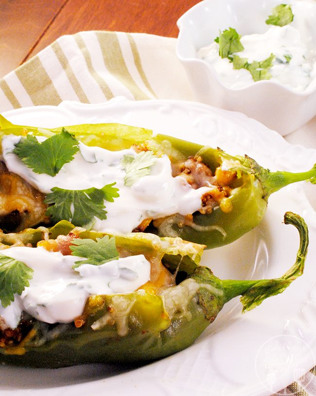 Stuffed Hatch Chiles - A spicy sweet stuffed Hatch chile with quinoa and corn topped with cheese and served with a cilantro honey yogurt sauce that will awaken your taste buds.