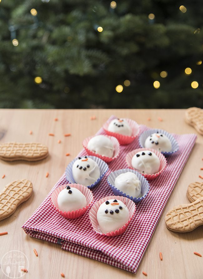 Nutter Butter Snowman Truffles - These adorable nutter butter cookie and cream cheese truffles are dipped in white chocolate and decorate to look like snowmen!