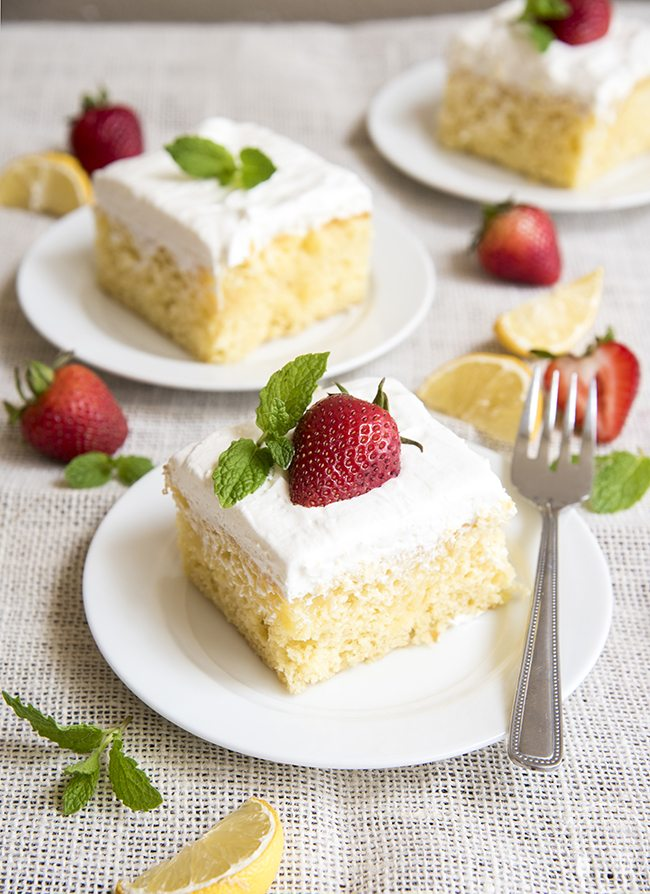 Lemon Poke Cake - This cake is perfectly refreshing. Its filled with lemon curd and topped with creamy whipped cream for the perfect spring or summer dessert!
