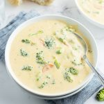 A bowl of broccoli cheese soup, with pieces of broccoli peeking out of the cheesy, creamy, soup.