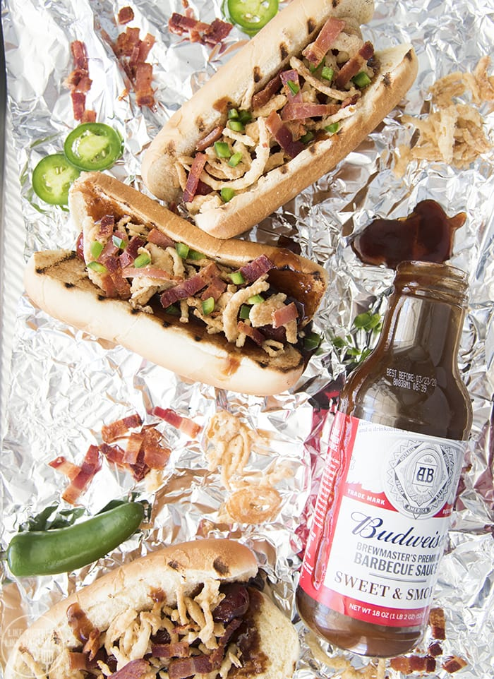 These BBQ Hot Dogs are topped with Budweiser's tangy Sweet &Smoky BBQ sauce, crispy onion straws, salty bacon, and spicy jalapenos for a delicious twist that is perfect to eat all summer long!
