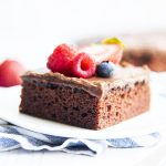 A slice of chocolate sheet cake on a plate, and topped with fresh berries