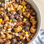 An overhead shot of a white bowl full of a Reeses Snack Mix, it has pretzels, peanuts, chocolate chips, peanut butter chips, reeses pieces, and mini reeses cups.