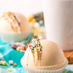A white hot chocolate bomb in a muffin liner topped with rainbow colored sprinkles, and a mug of cocoa behind it.