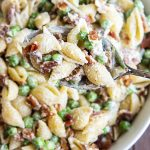 A close up of pasta salad with medium shells, bacon, and peas covered in a creamy white sauce.